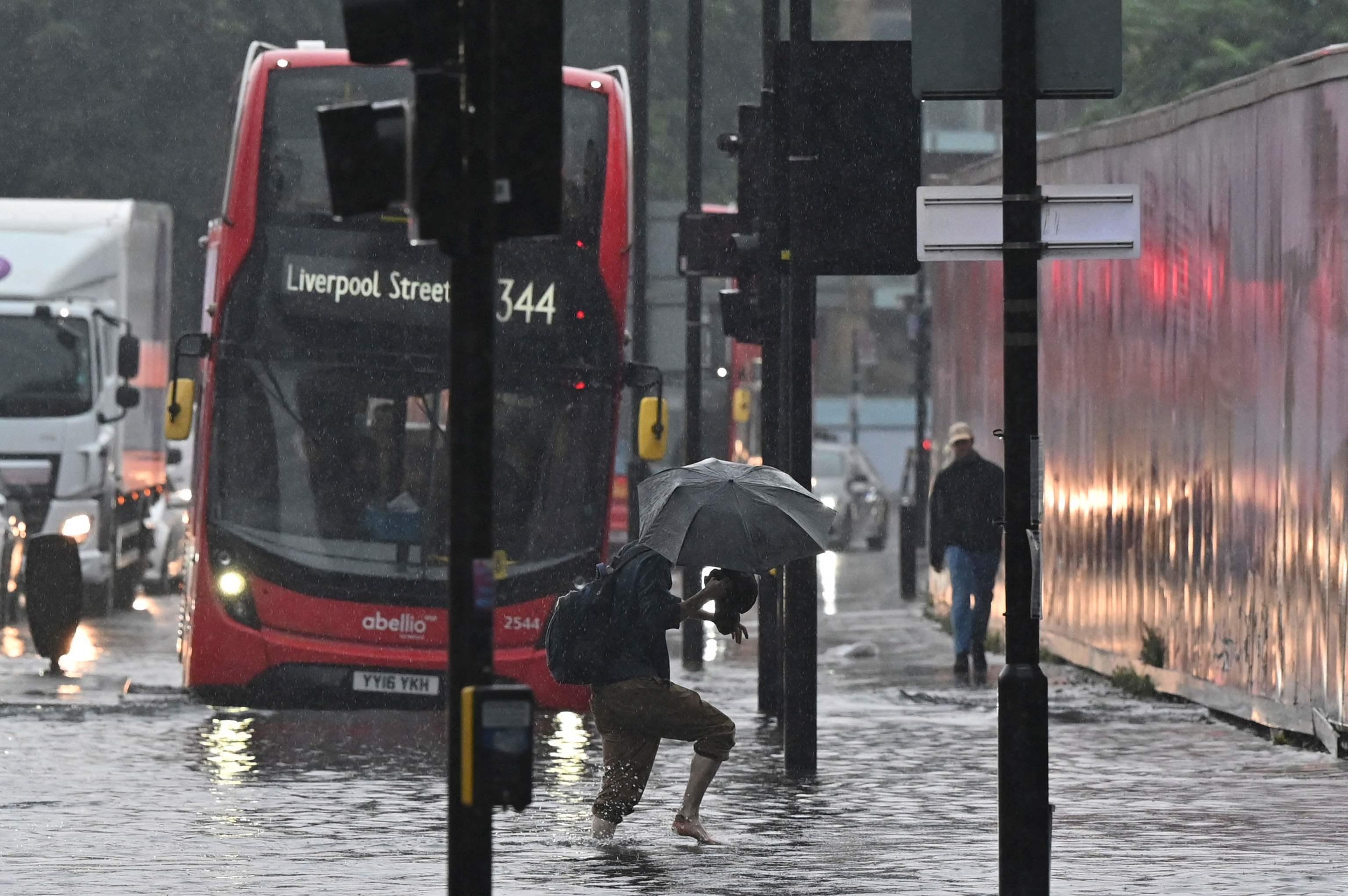 Un peatón cruza la calzada inundada en Londres el 25 de julio