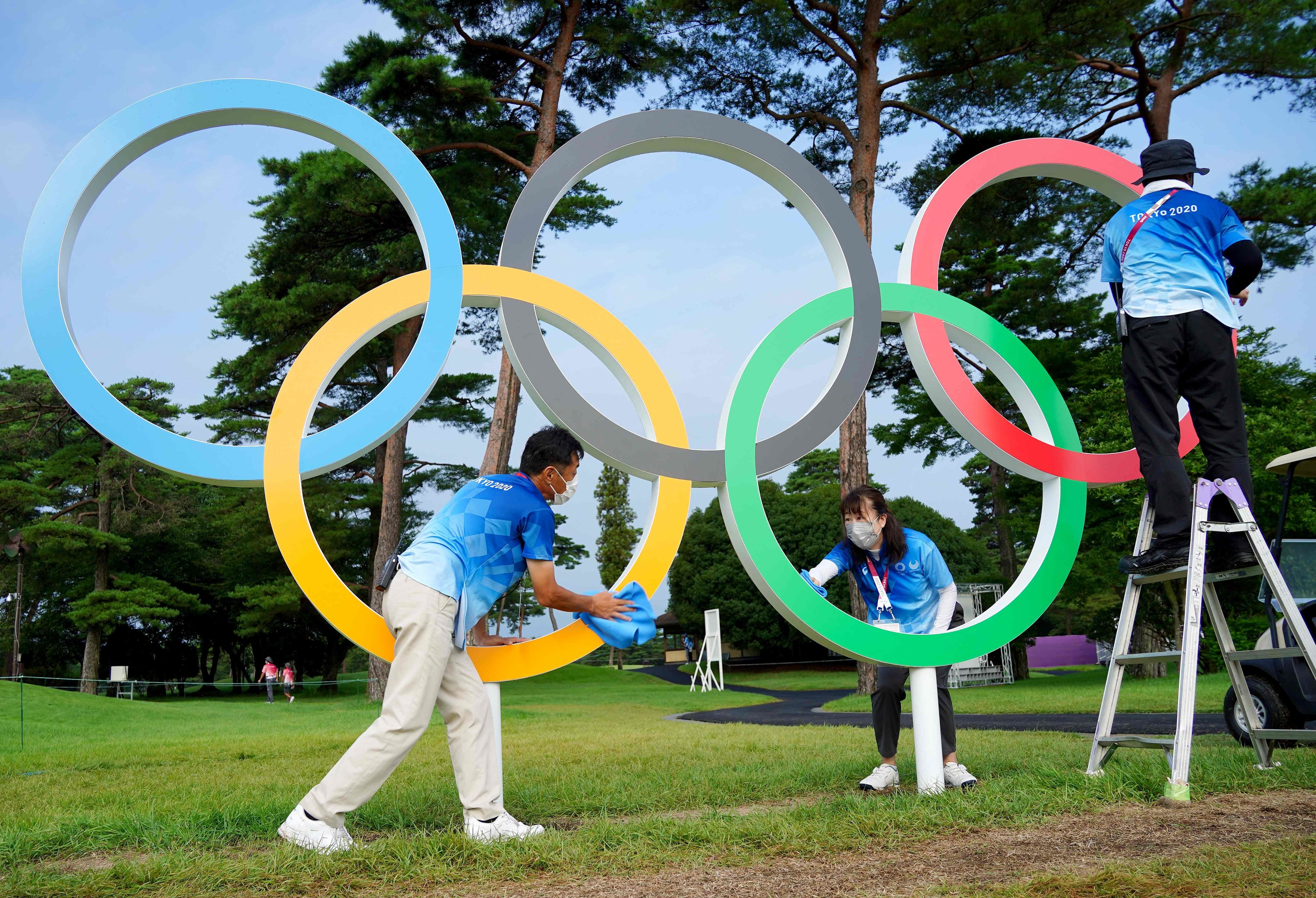 Voluntarios limpiando los aros olímpicos del Kasumigaseki Club.