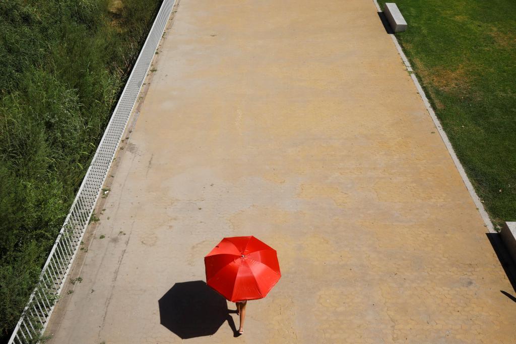 Una joven se protege del sol bajo un paraguas en Córdoba.