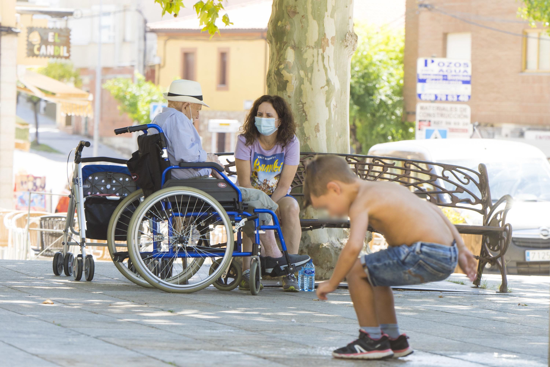 Un niño juega en un pueblo de Cáceres ante un hombre de la tercera edad y su acompañante.