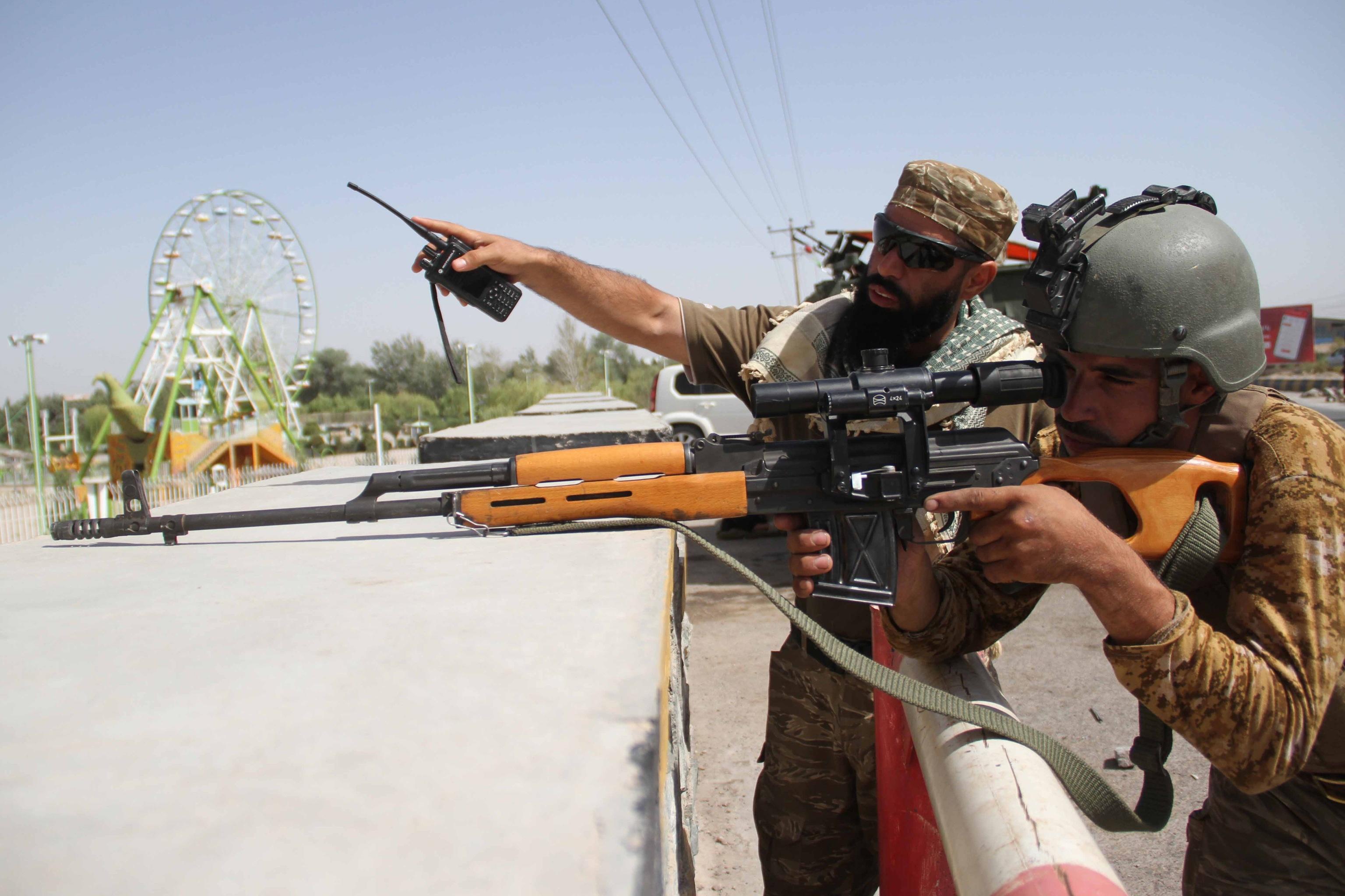Dos militares afganos tratan de combatir a los talibán en las afueras de Herat.