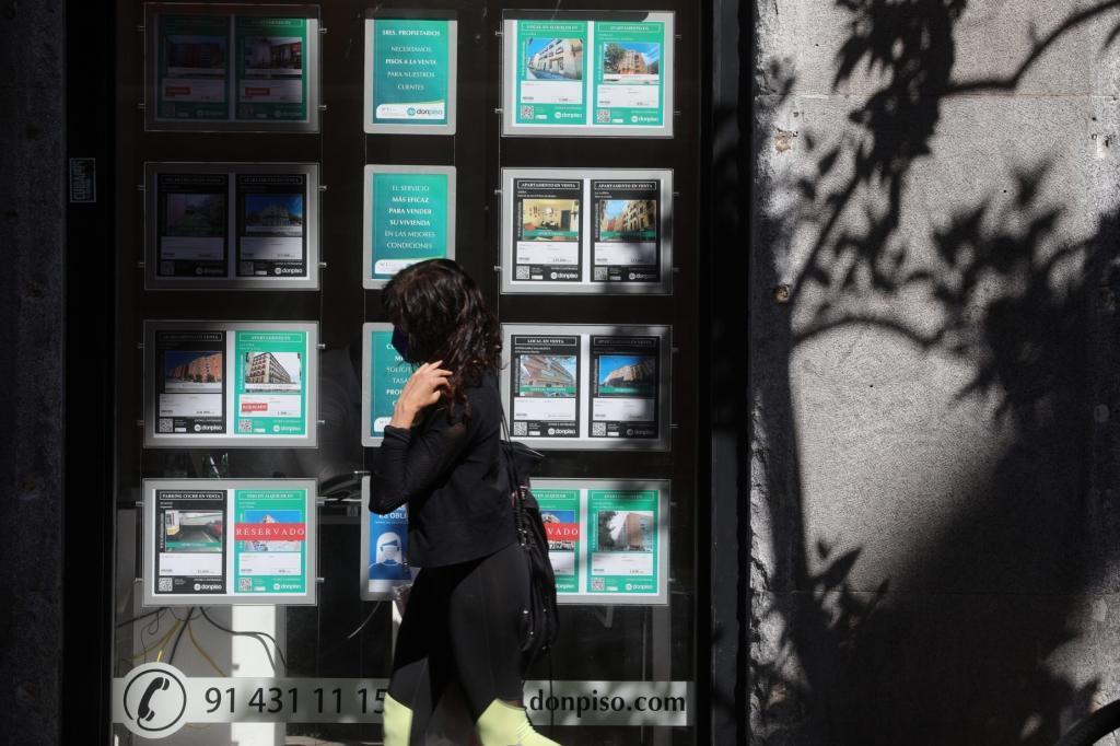 Una mujer camina ante unos anuncios de alquiler de una inmobiliaria.