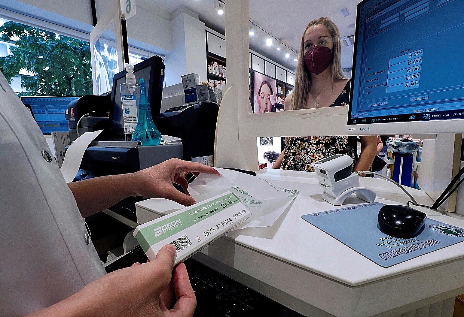 Una mujer compra un test de Covid en una farmacia.