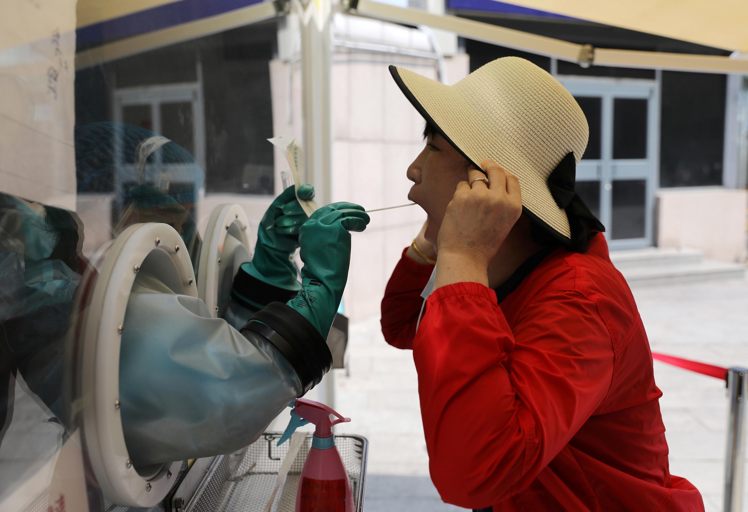 Un trabajador médico toma una muestra para una PCR en una estación de tren en Beijing, en China.