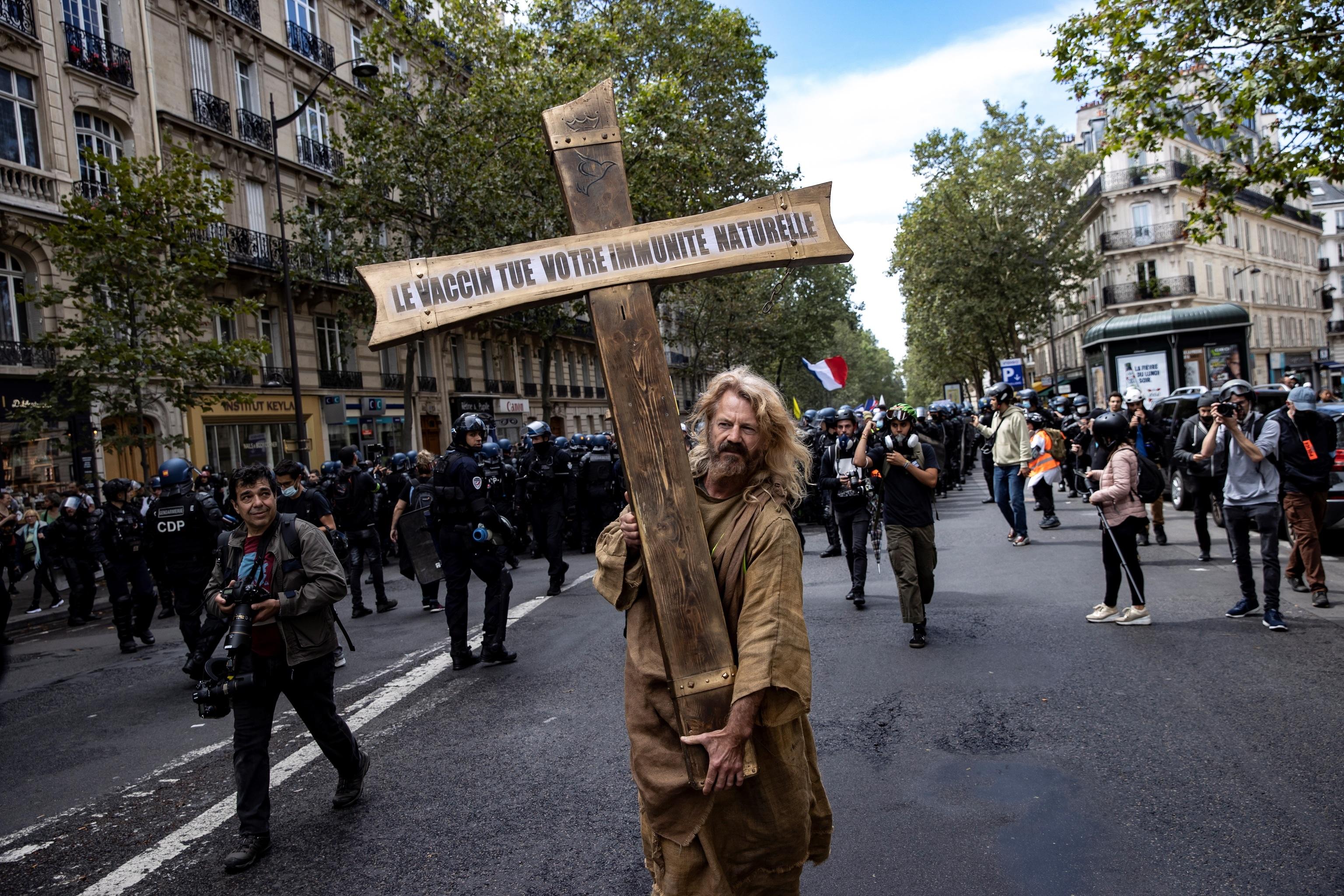 Un manifestante en París vestido como Jesucristo con una cruz con el mensaje 'La vacuna mata tu sistema inmune'.