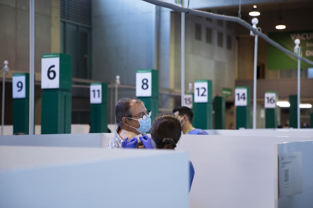Un hombre recibe la vacuna en el punto instalado en el estadio de la Cartuja de Sevilla.