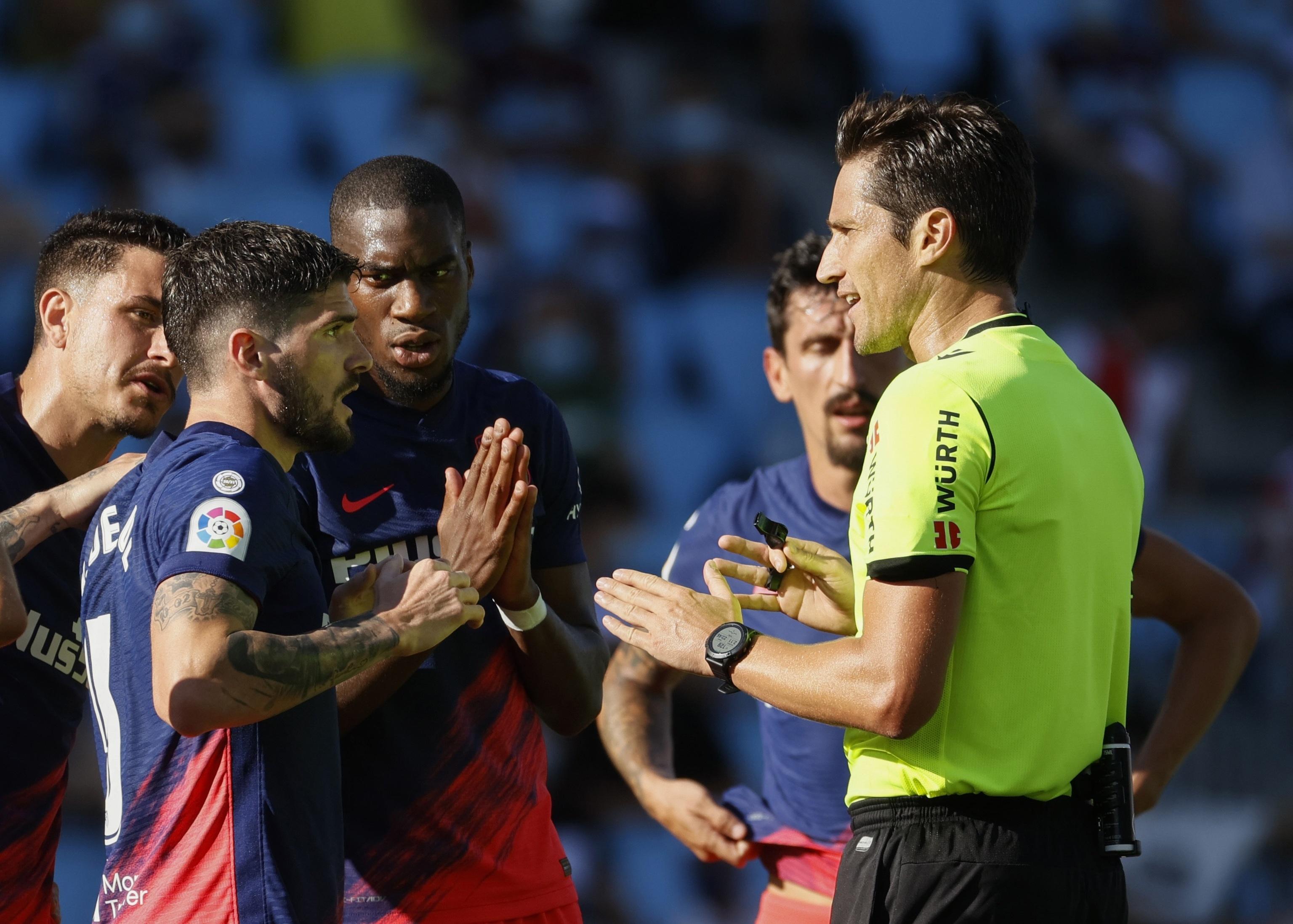 Los jugadores del Atlético discuten con Munuera Montero.