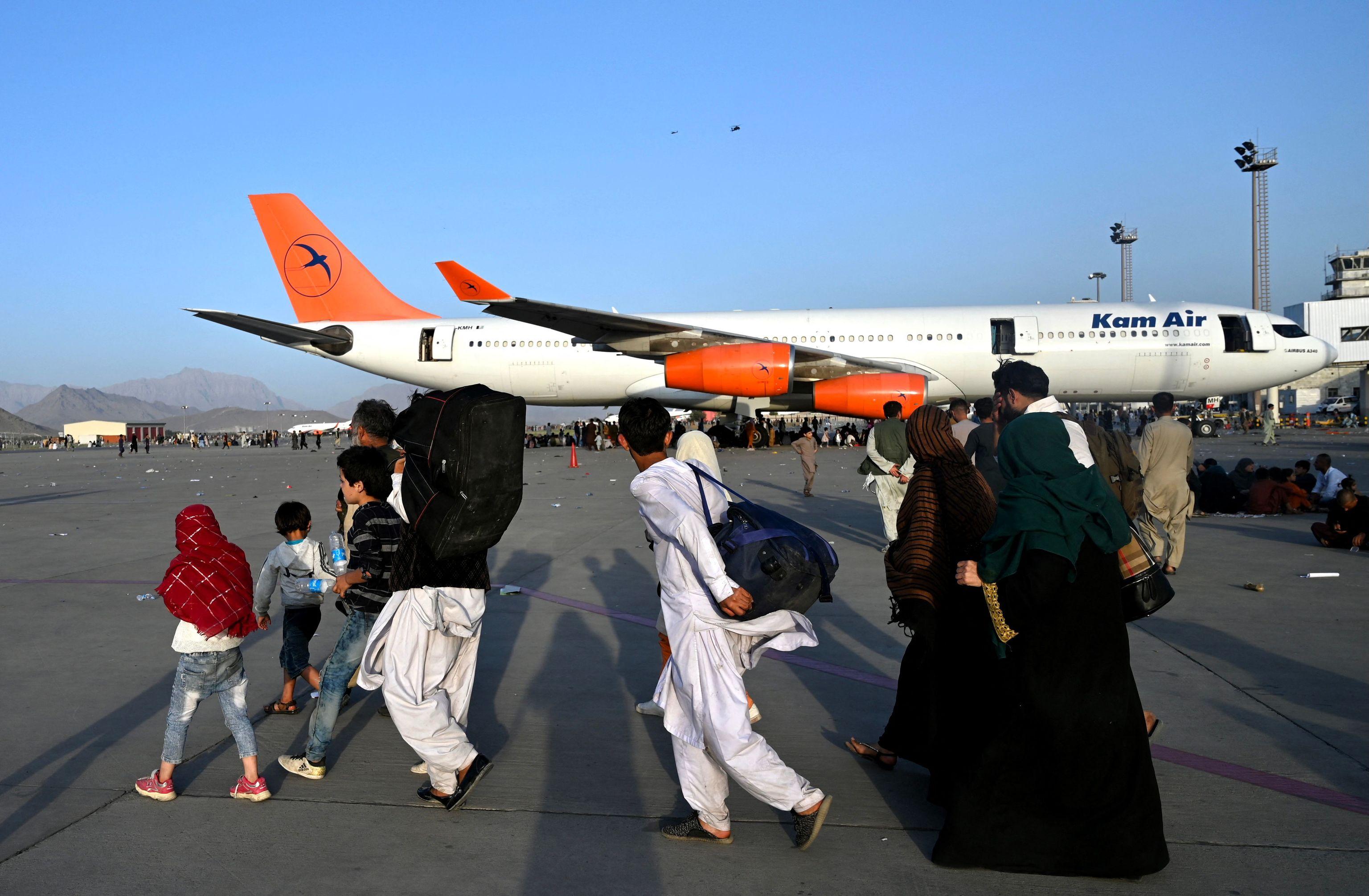 Familias afganas embarcan en distintos vuelos, en el aeropuerto de Kabul.