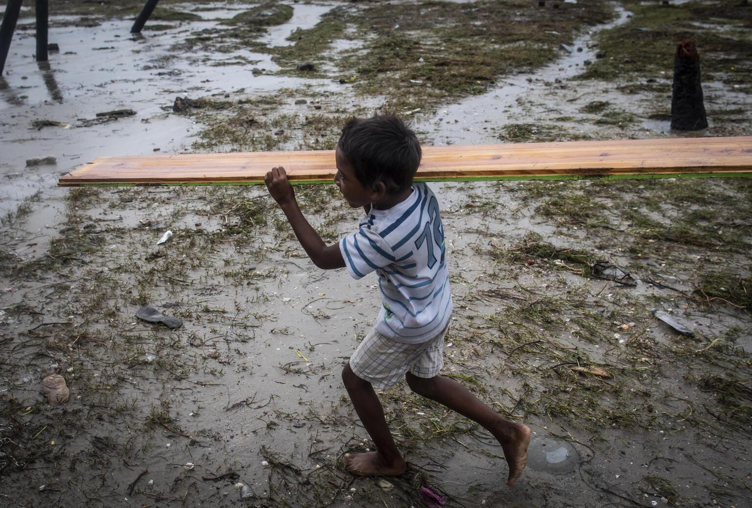 Un niño de Puerto Cabezas (Nicaragua) ayuda a sus padres a reconstruir su casa tras el paso del huracán Iota, en noviembre de 2020