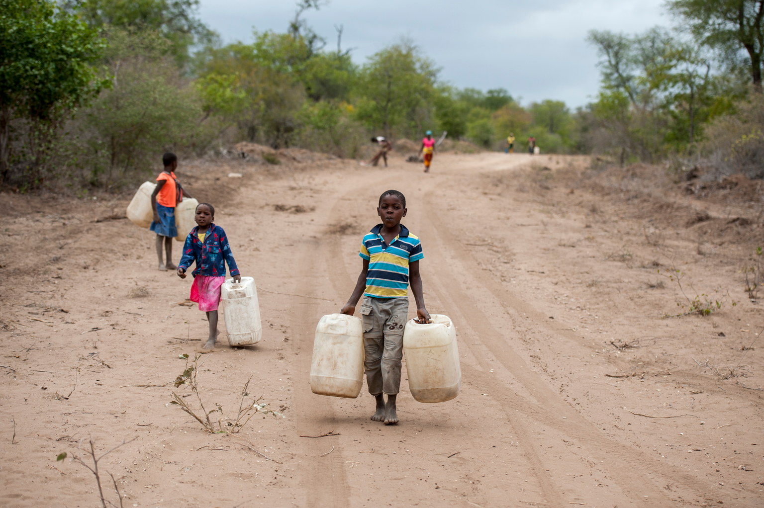 Niños transportan agua en bidones en Mozambique