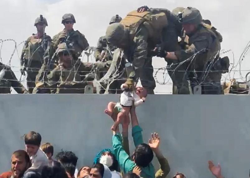 Un afgano entrega a su bebé los soldados de EEUU a través de la alambrada del aeropuerto de Kabul.