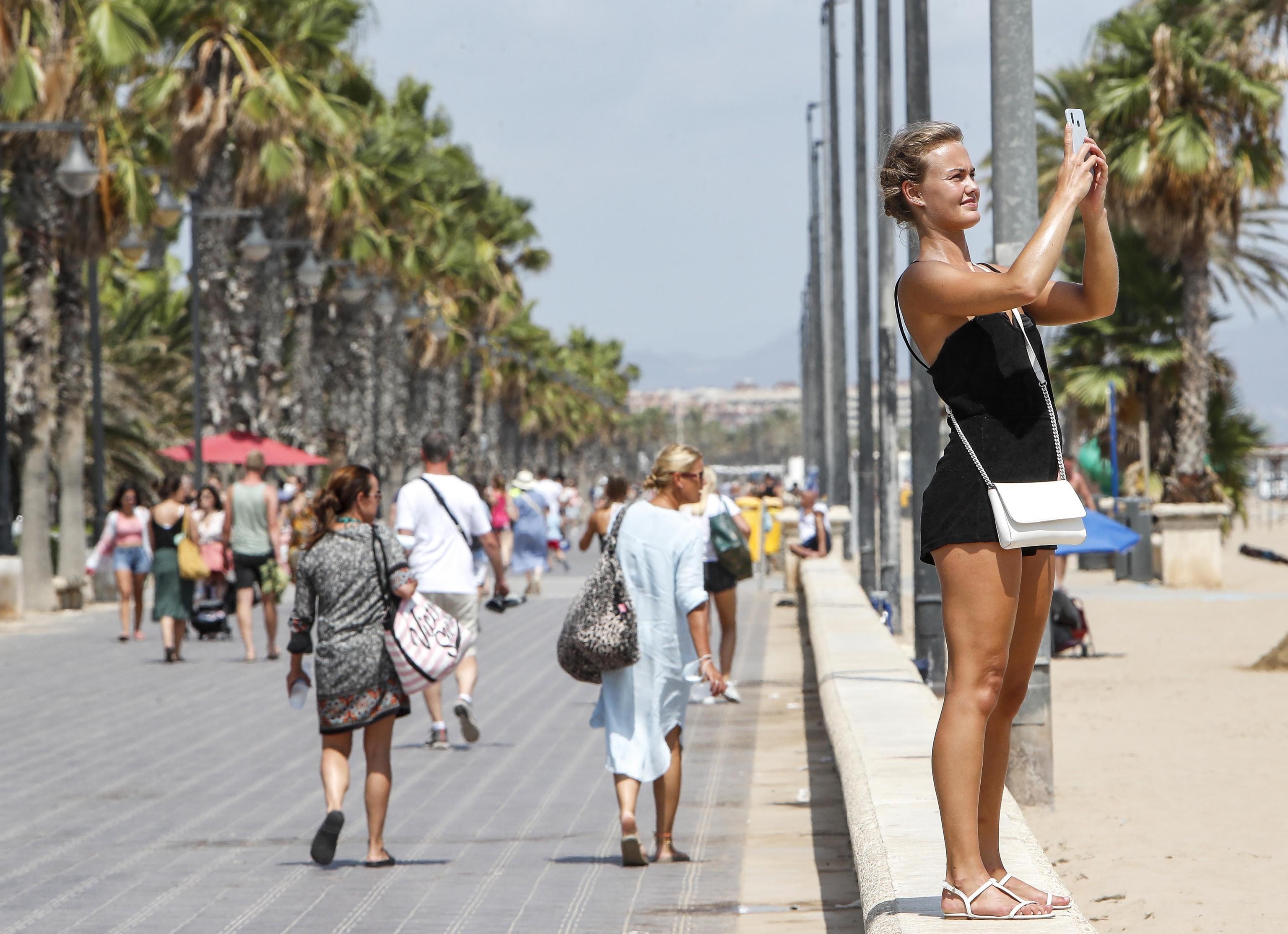 Una mujer se fotografía en el paseo marítimo de Valencia el pasado mes de agosto.