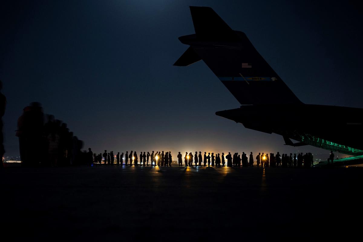 Cientos de afganos esperan para subir a un avión de EEUU en Kabul.