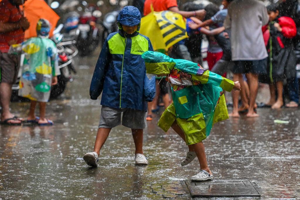Un grupo de niños juega en la lluvia en India.