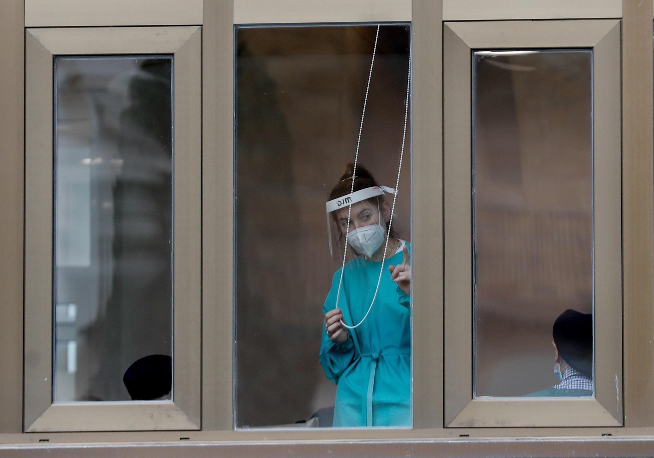 La trabajadora de una residencia de ancianos de Zarautz observa desde la ventana el acto de homenaje a las personas fallecidas con covid-19 en los geriátricos del territorio celebrado este viernes en la localidad guipuzcoana.