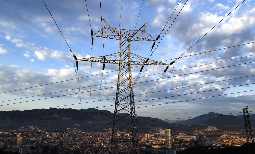 Una torre de Red Eléctrica, con la ciudad de Bilbao al fondo.