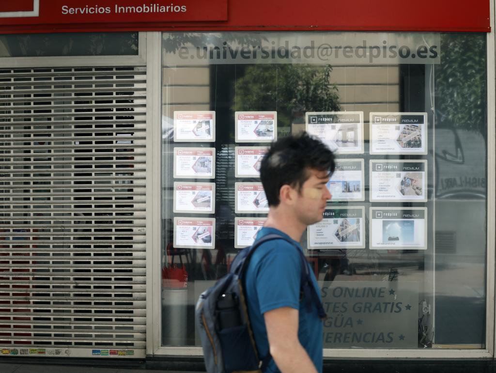 Un joven camina delante de una agencia inmobiliaria, en Madrid.
