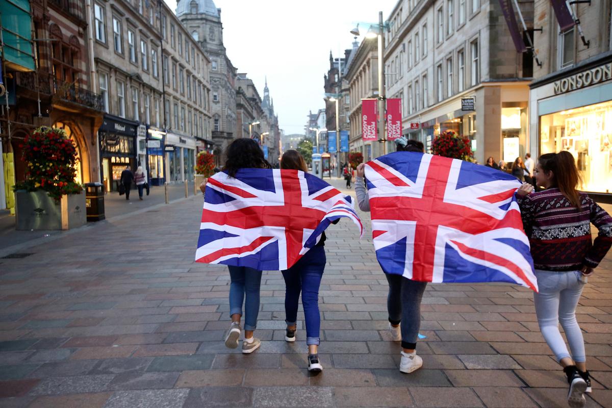 Un grupo de jóvenes pasea con banderas británicas, en Glasgow.