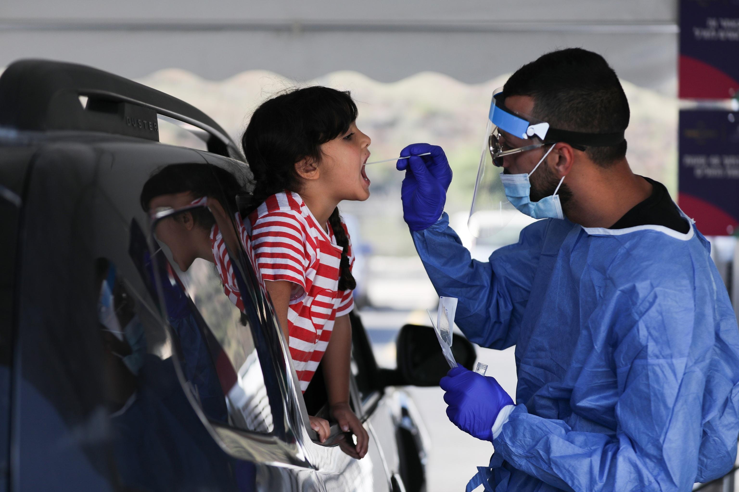 Un profesional sanitario recoge una muestra de saliva para un test Covid en un coche.