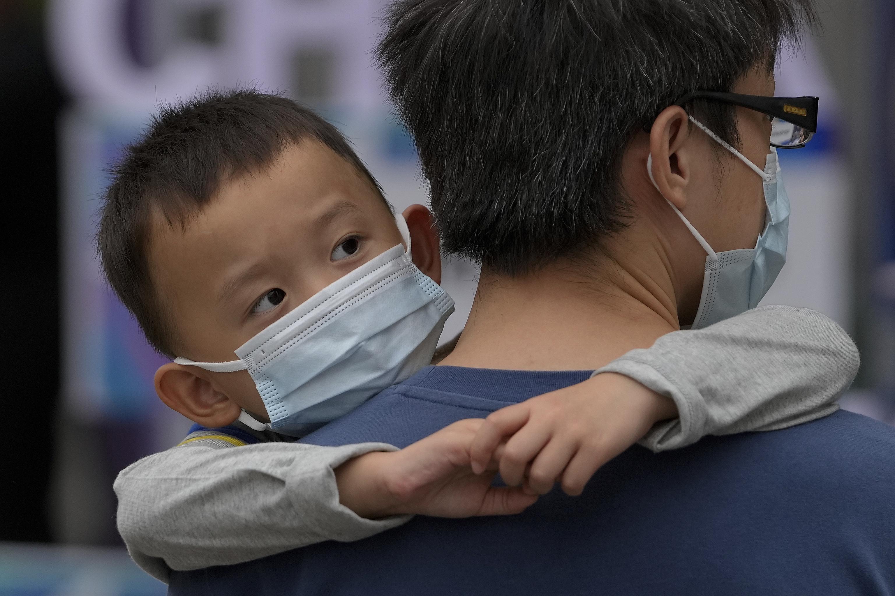 Un hombre lleva en brazos a un niño, ambos protegidos con mascarilla, en las calles de Pekín.