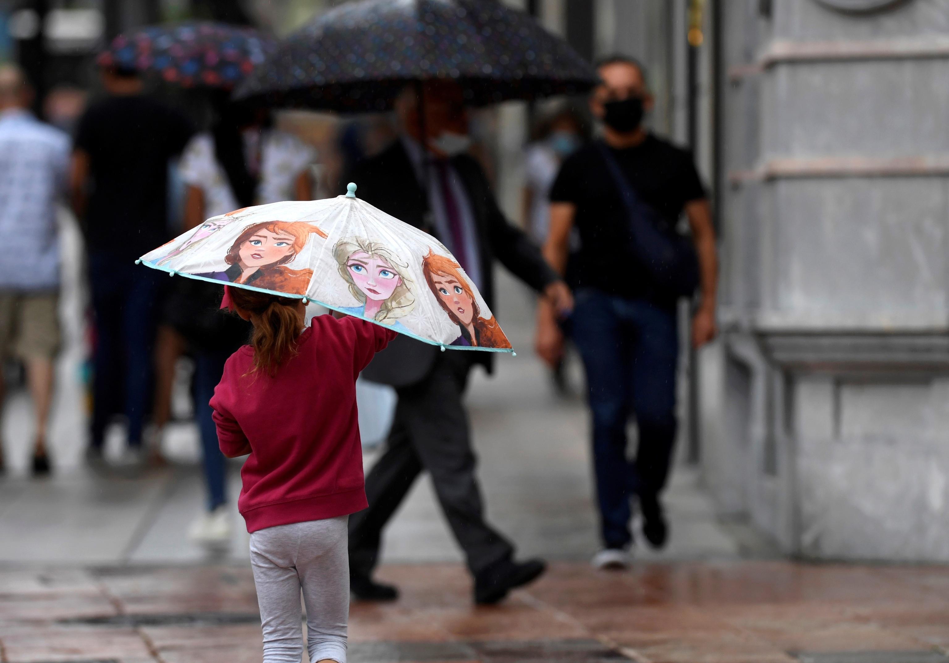 Una niña se protege de la lluvia en Oviedo.