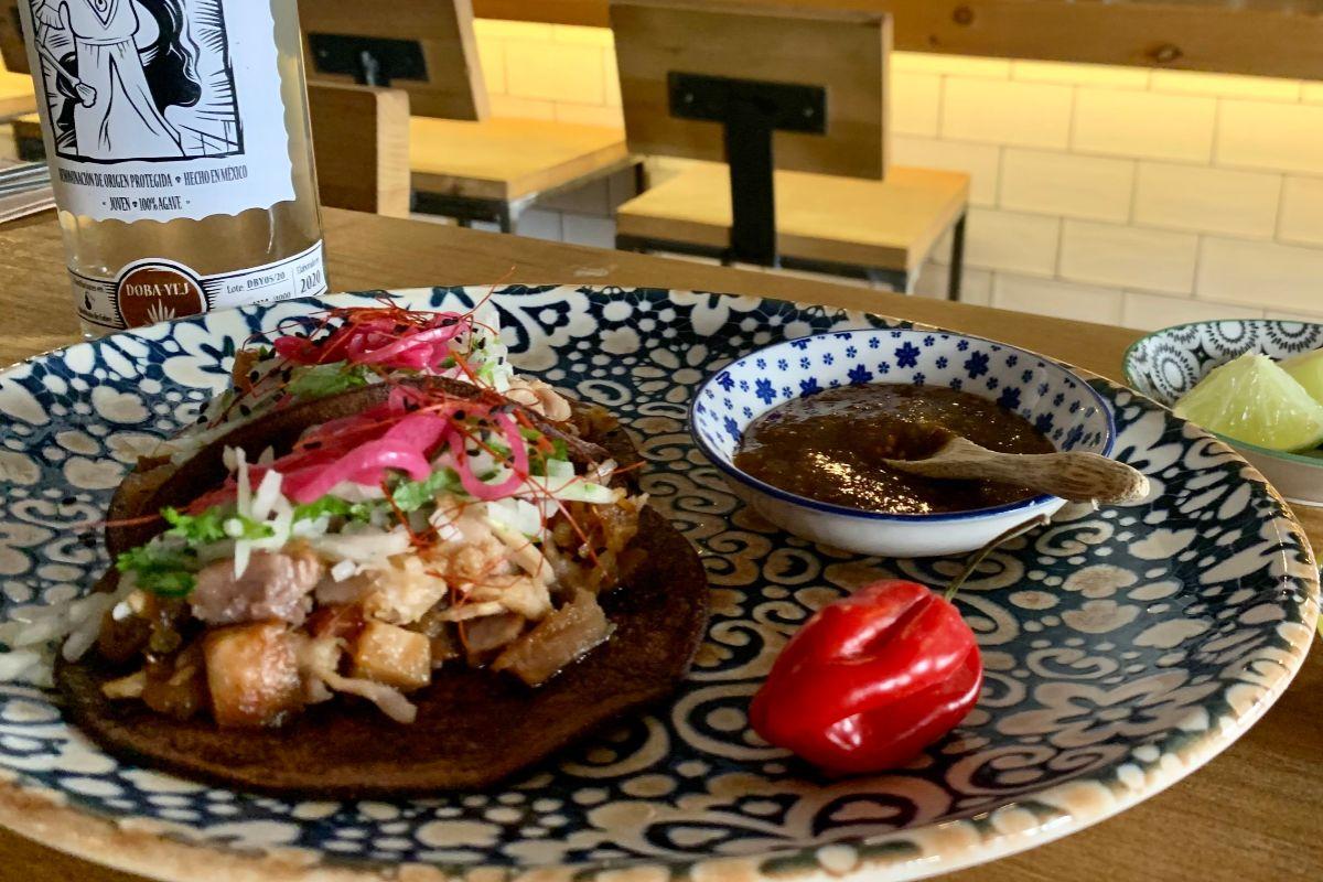 Tacos de carnitas en tortilla de maíz azul con salsa de chile morita, en La Tomata.