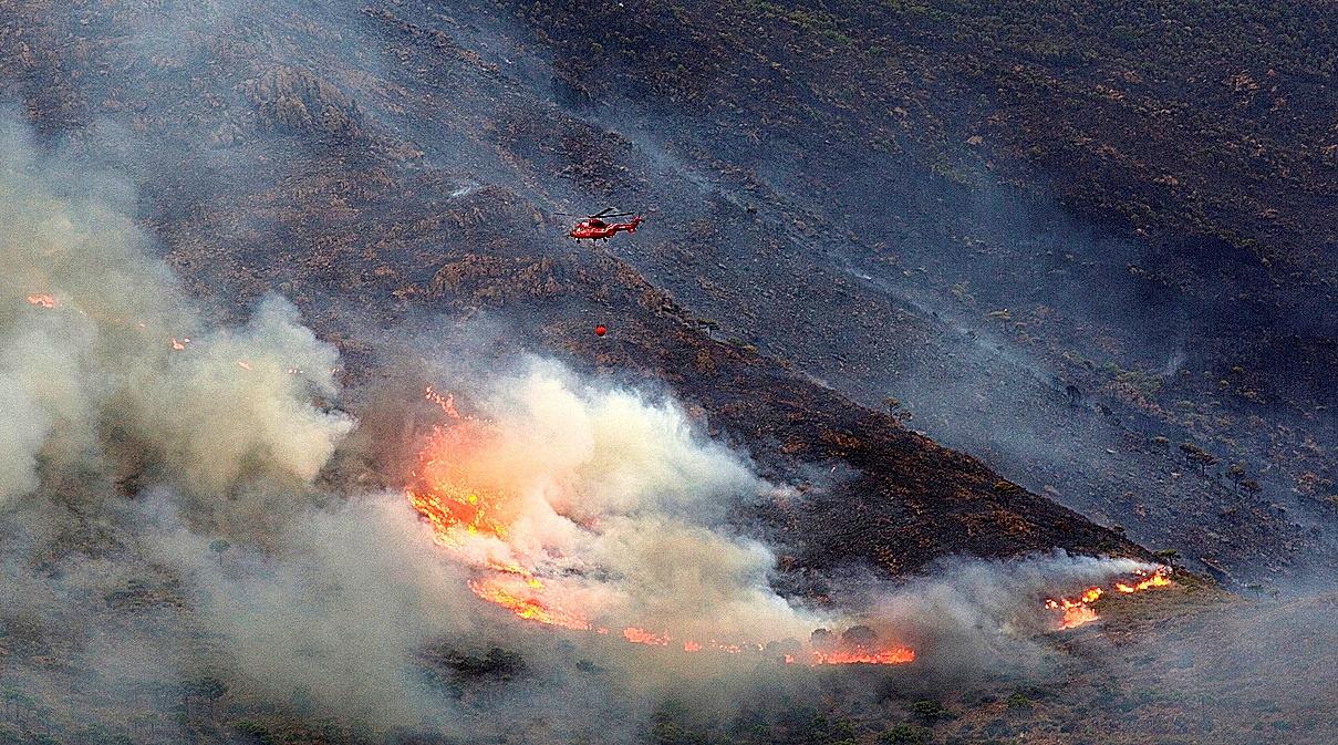 Un helicóptero sobrevuela un foco del incendio de Sierra Bermeja.