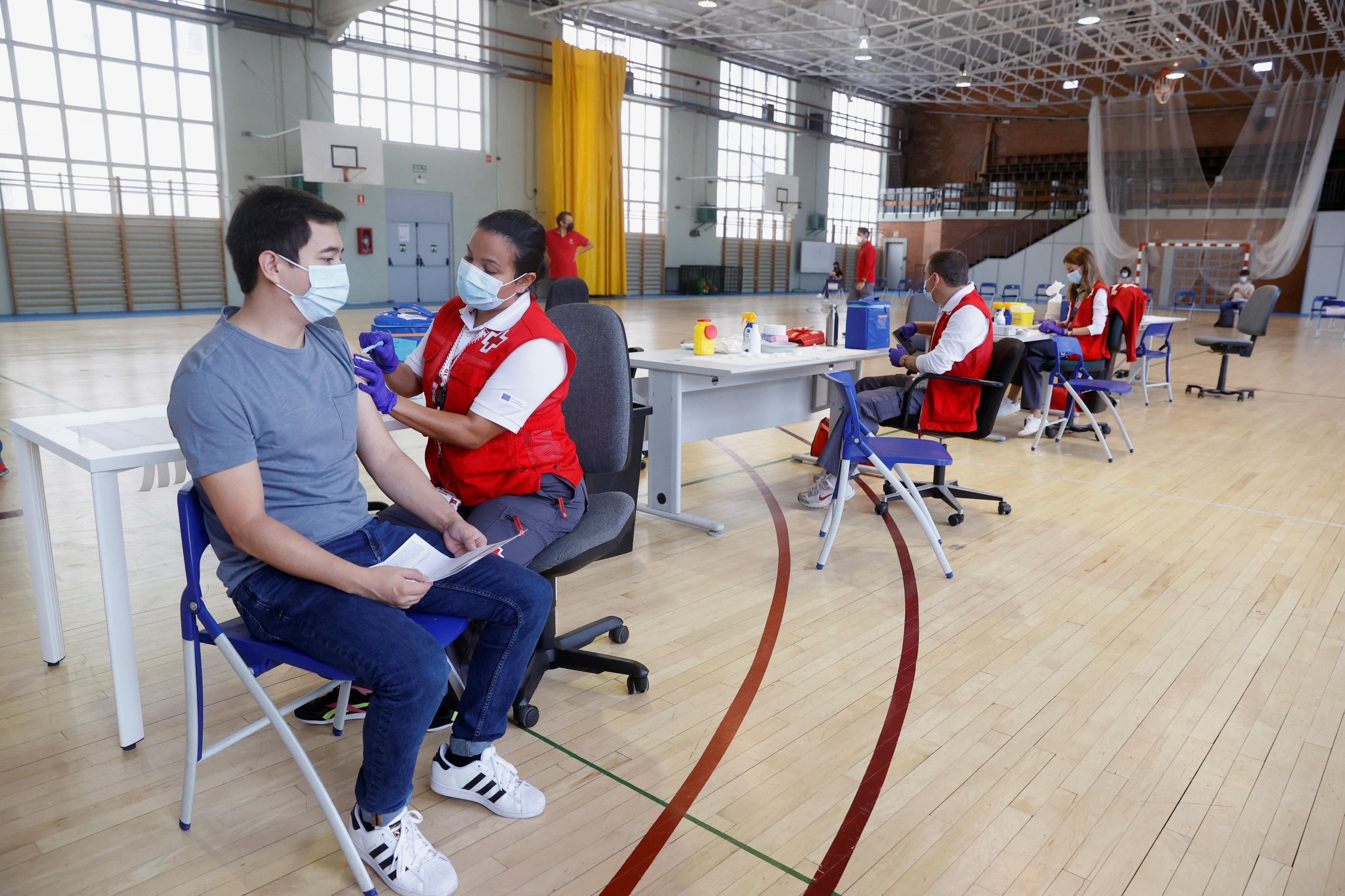 Un joven recibe la vacuna en el polideportivo de la Almudena de la Universidad Complutense (UCM), este martes.