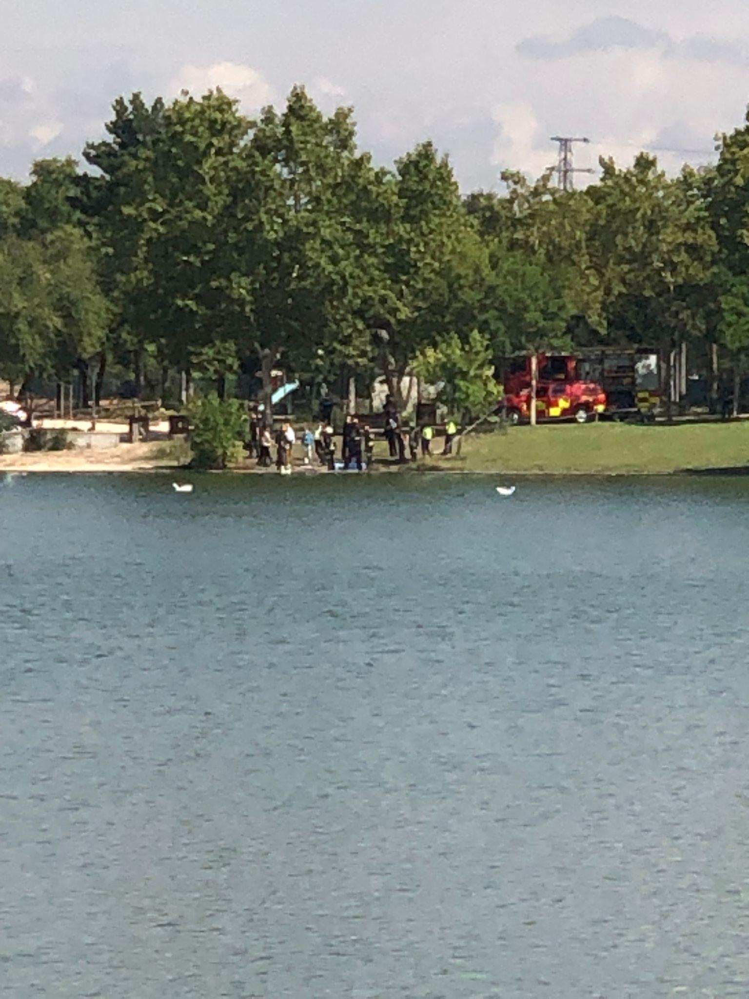 Policía Nacional y  bomberos en el lugar del hallazgo en el lago del parque de Polvoranca de Leganés.