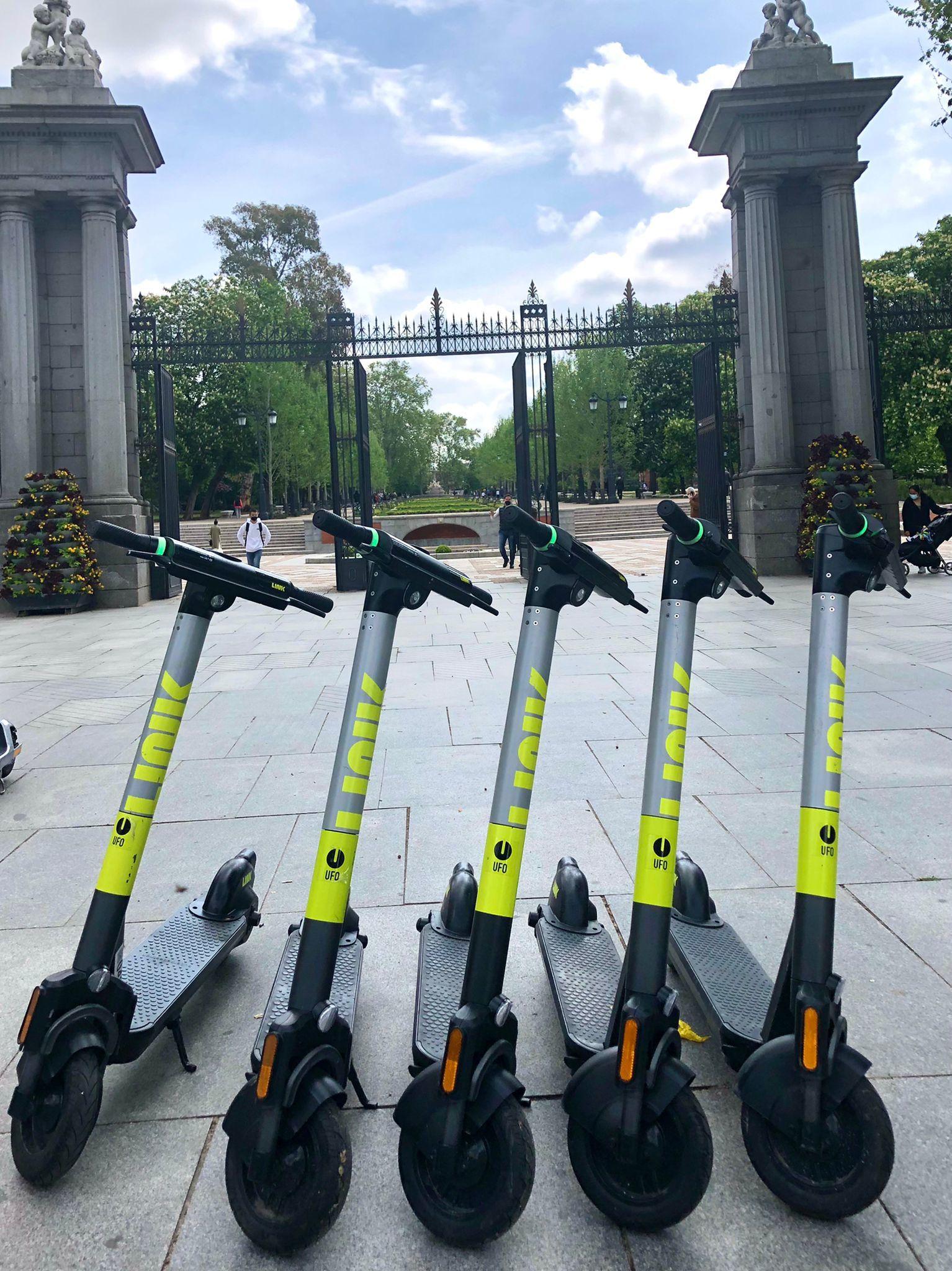 Varios de los patinetes Link aparcados frente una entrada del parque de El Retiro