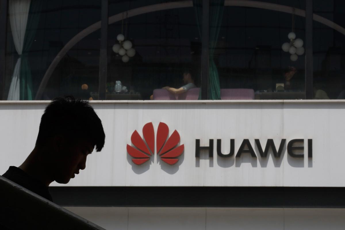 Un hombre camina al lado del logo de Huawei, en Pekín.