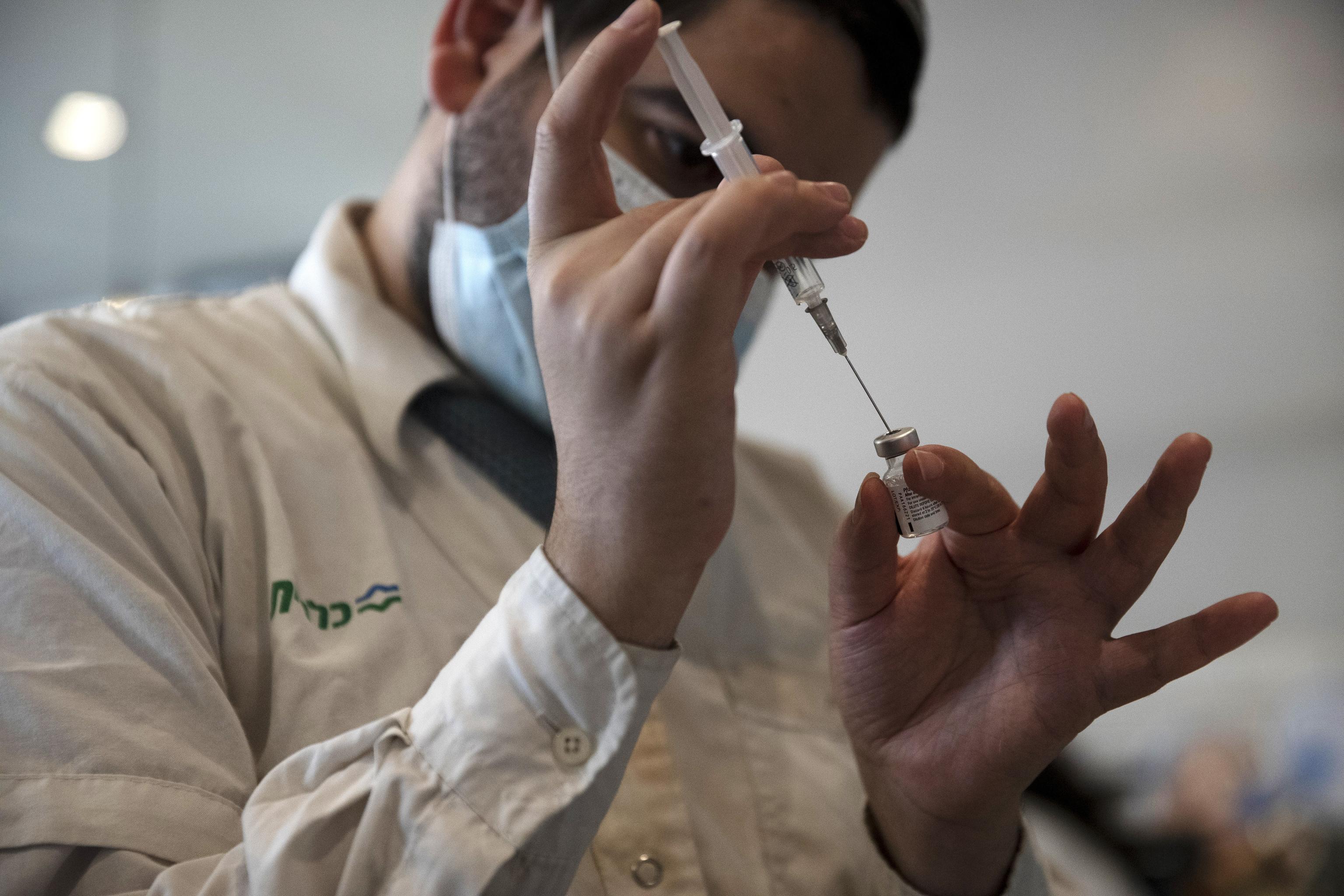 Un médico prepara un vial de Pfizer.
