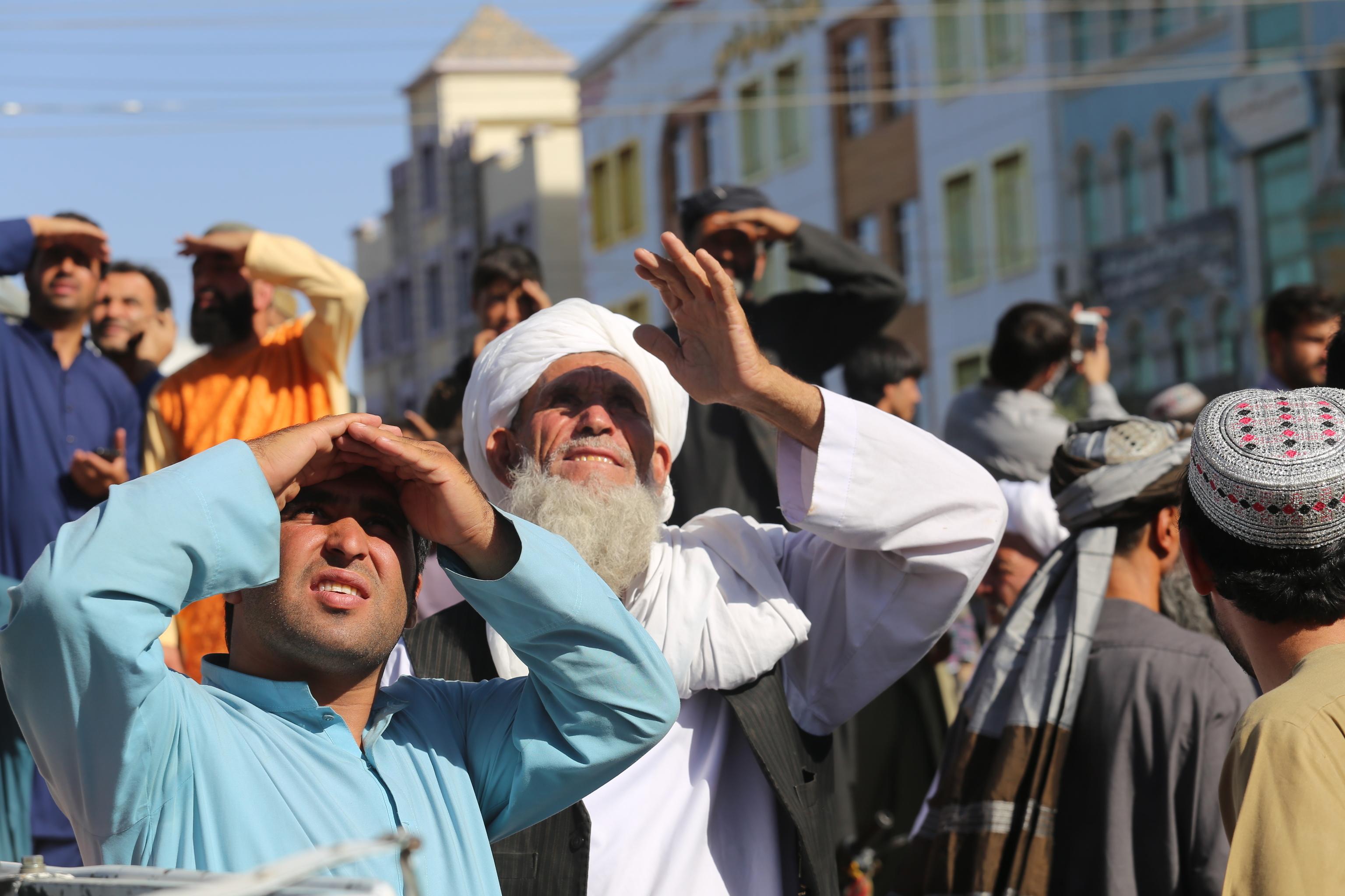 Afganos miran uno de los cuerpos colgados en Herat.