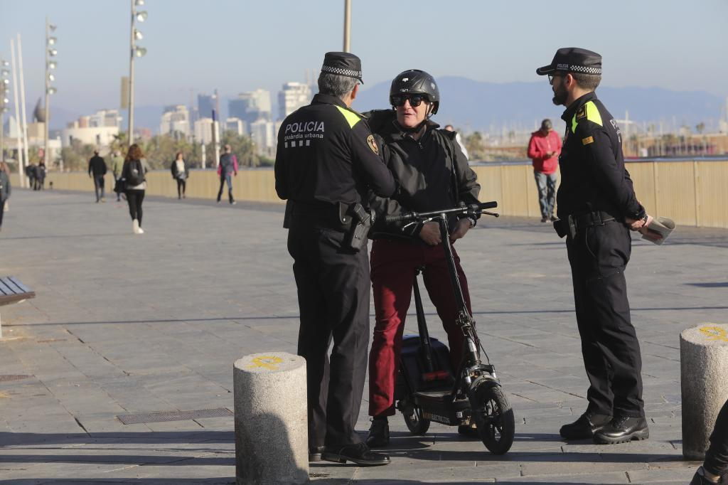 Agentes de la Guardia Urbana con una usuaria de patinete