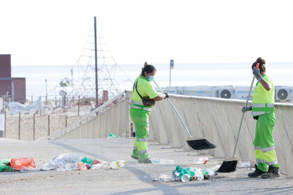 Dos trabajadoras de los servicios de limpieza recogen restos de un botellón.