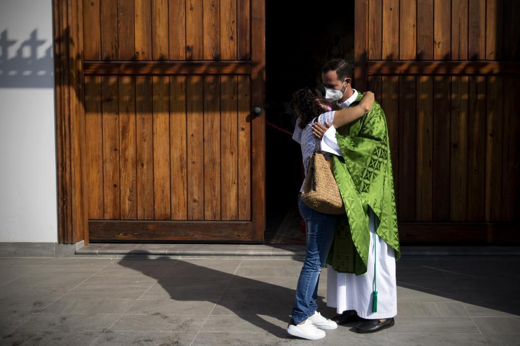 Don Alberto abraza a una feligresa esta mañana.