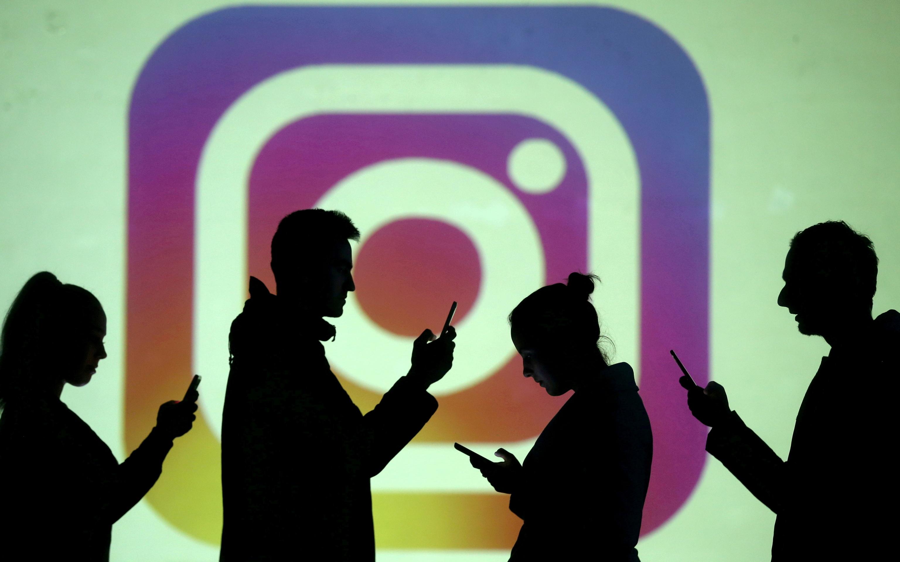 Varias personas revisan su móvil mientras cruzan por delante de un icono de Instagram.