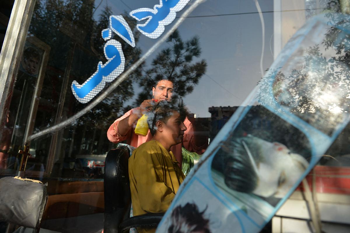Un hombre atiende a un cliente en su barbería de Herat.