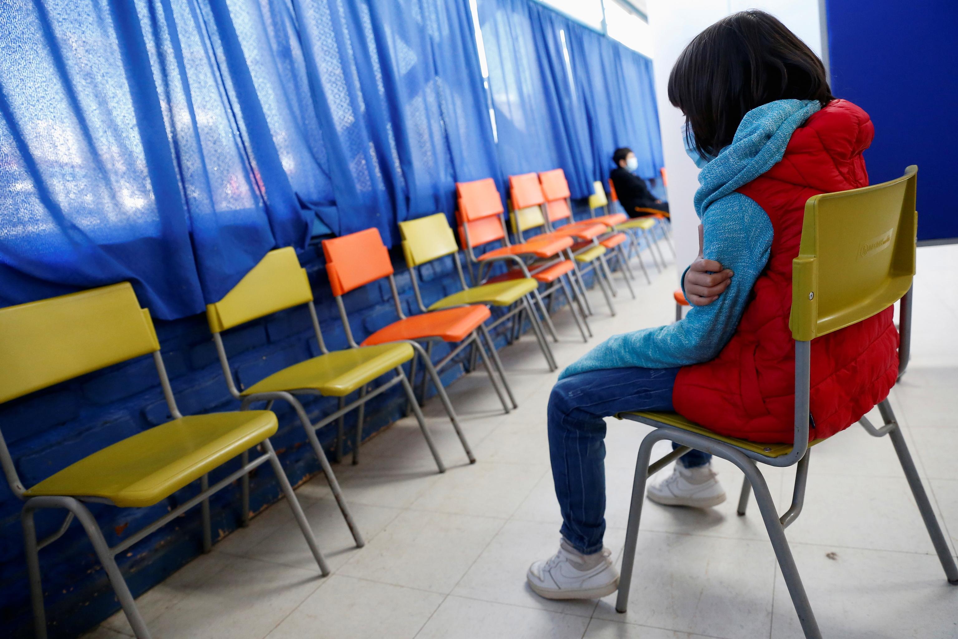 Una niña espera después de recibir la vacuna de Sinovac contra el coronavirus en un colegio público en Chile.