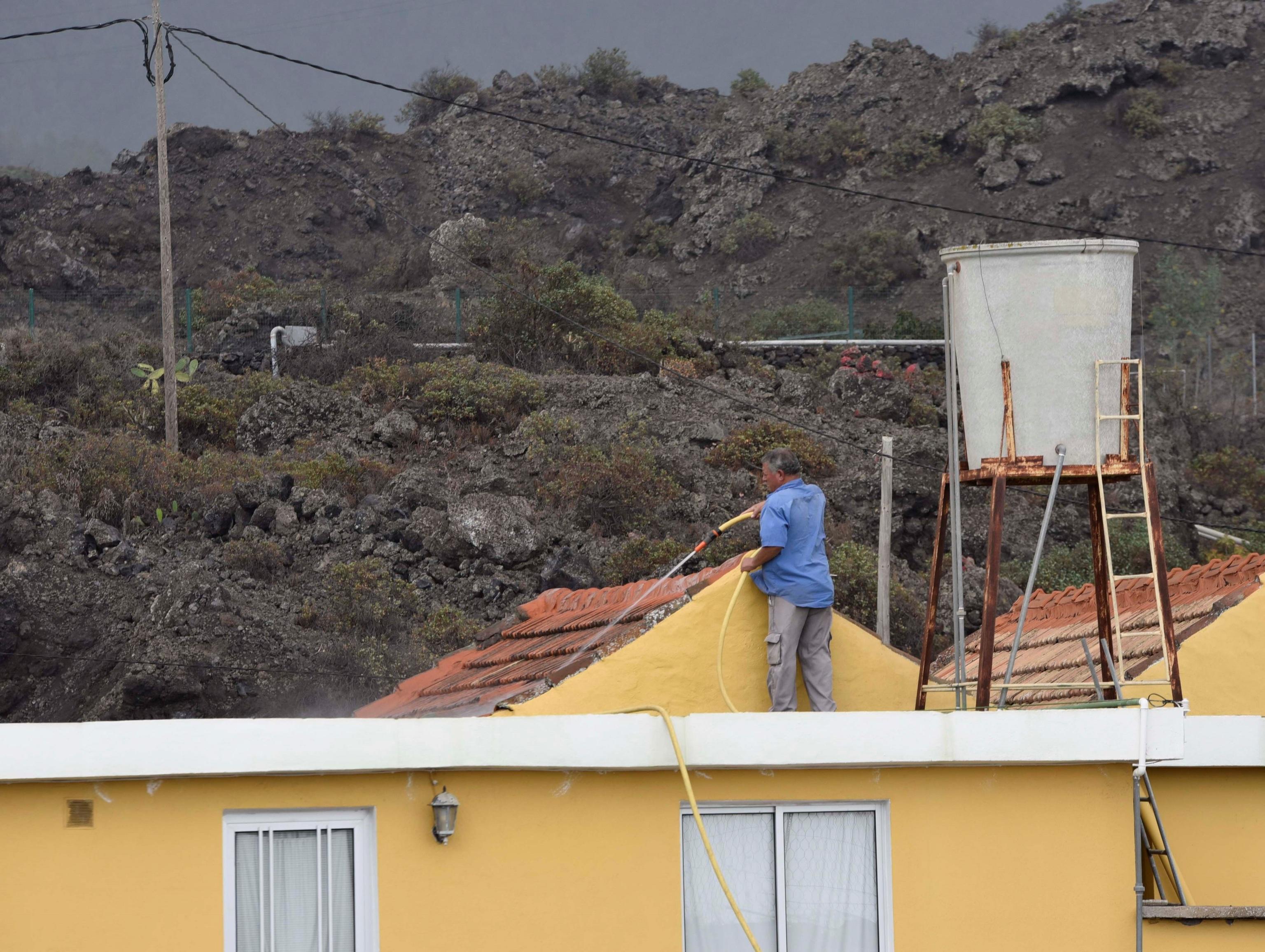 Un vecino de Tacande limpia con agua el tejado de su vivienda afectado por la caída de cenizas.