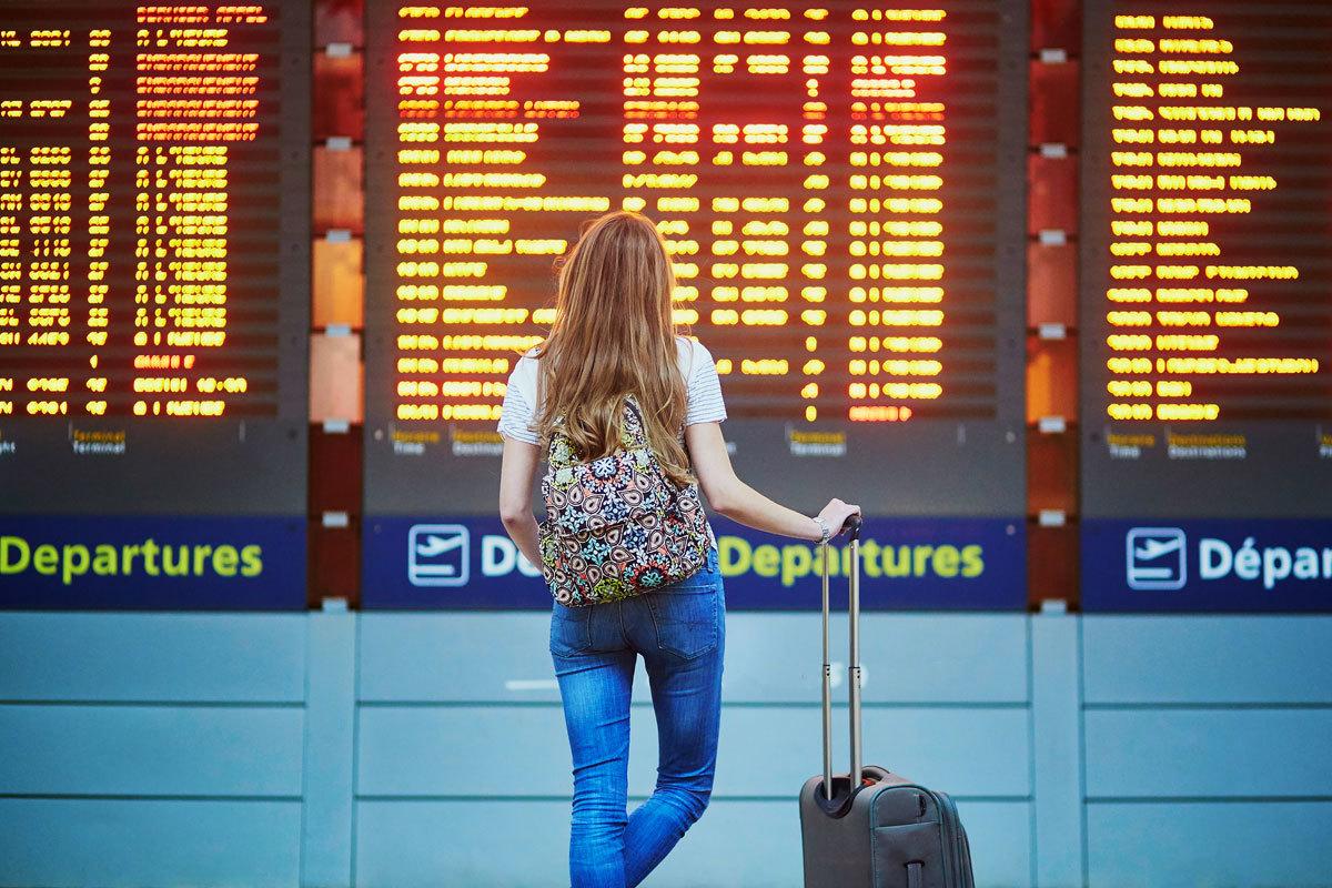 Una joven consulta el panel de salidas de un aeropuerto.