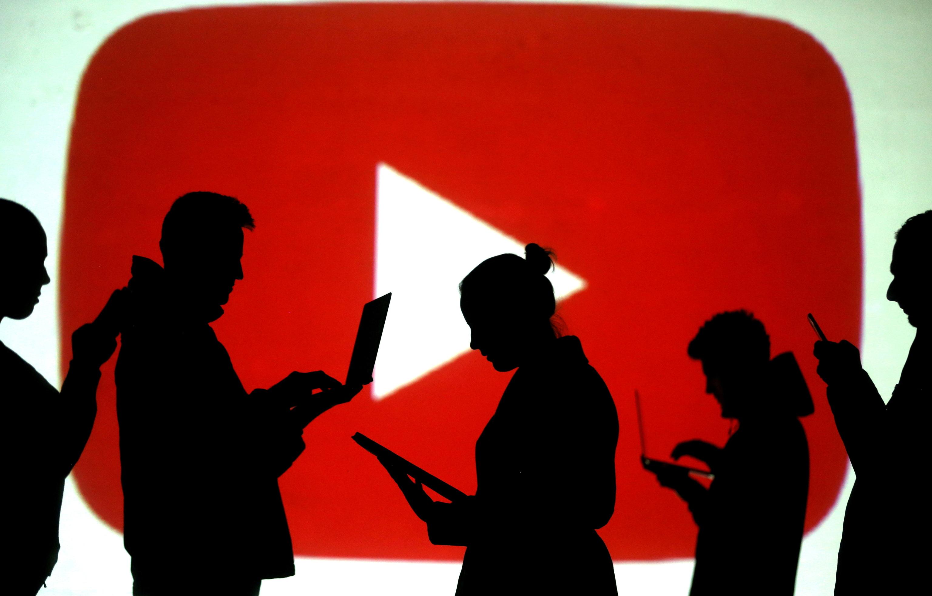 Siluetas con móviles y ordenadores ante el logo de YouTube.