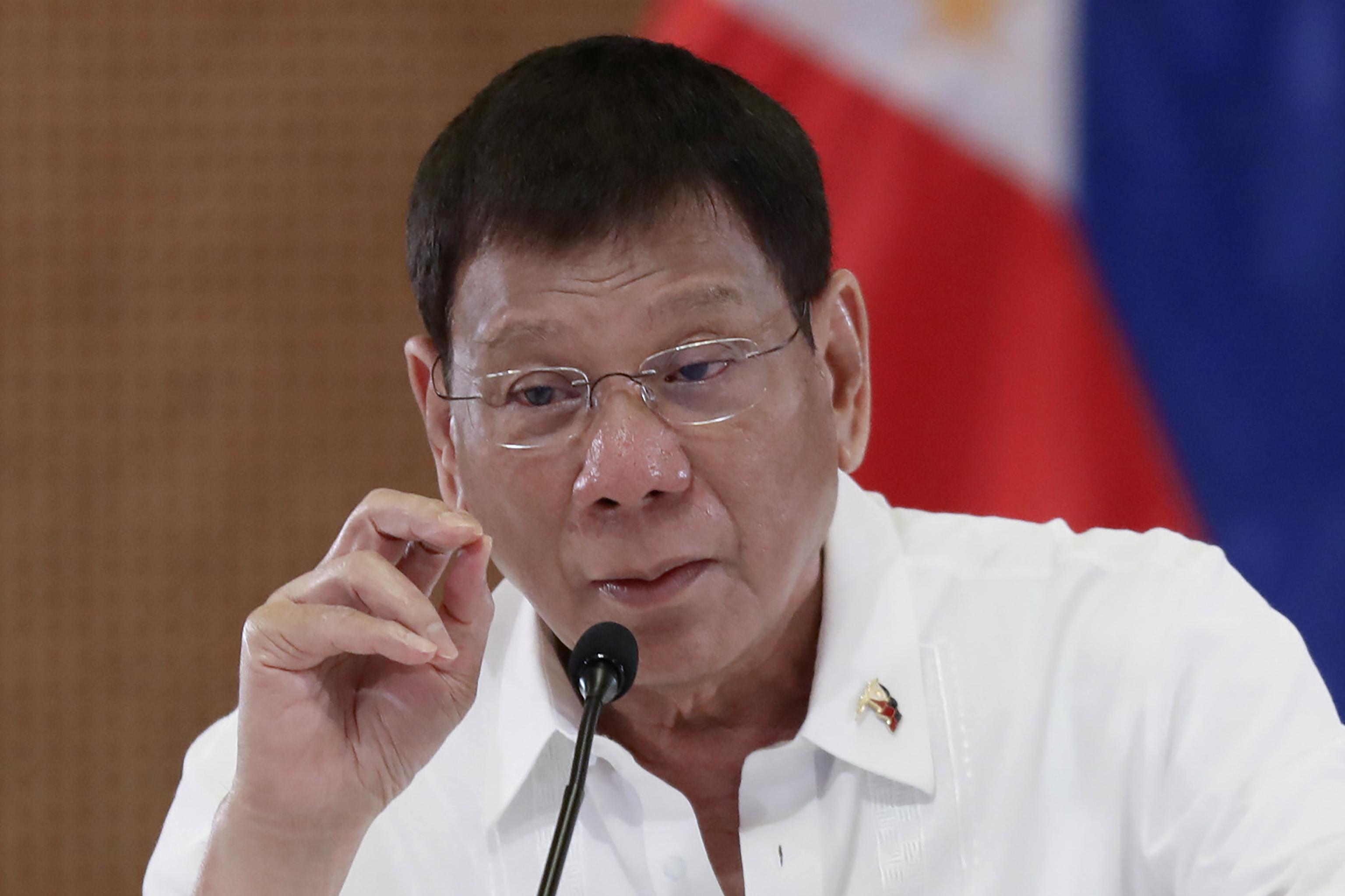 رودریگو دوترته ، رئیس جمهور فیلیپین در حالی که می خندد ، دست به حرکت می زند