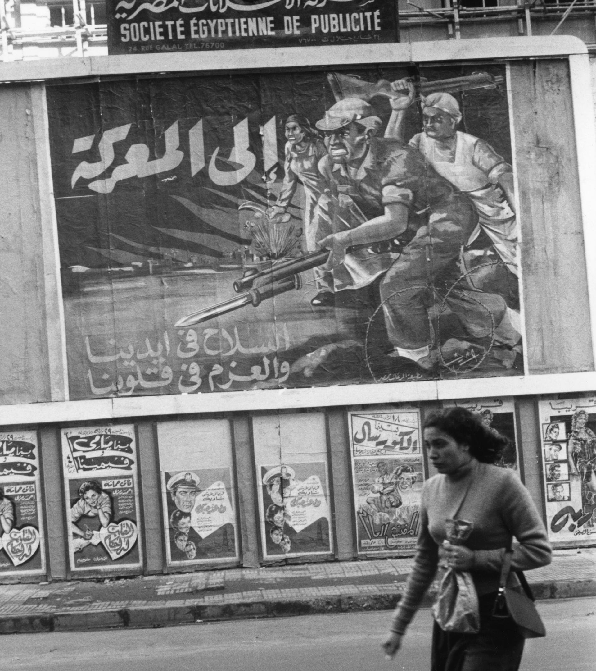 Una mujer en una calle de Alejandría con imágenes de propaganda de Nasser en EL año 1956.