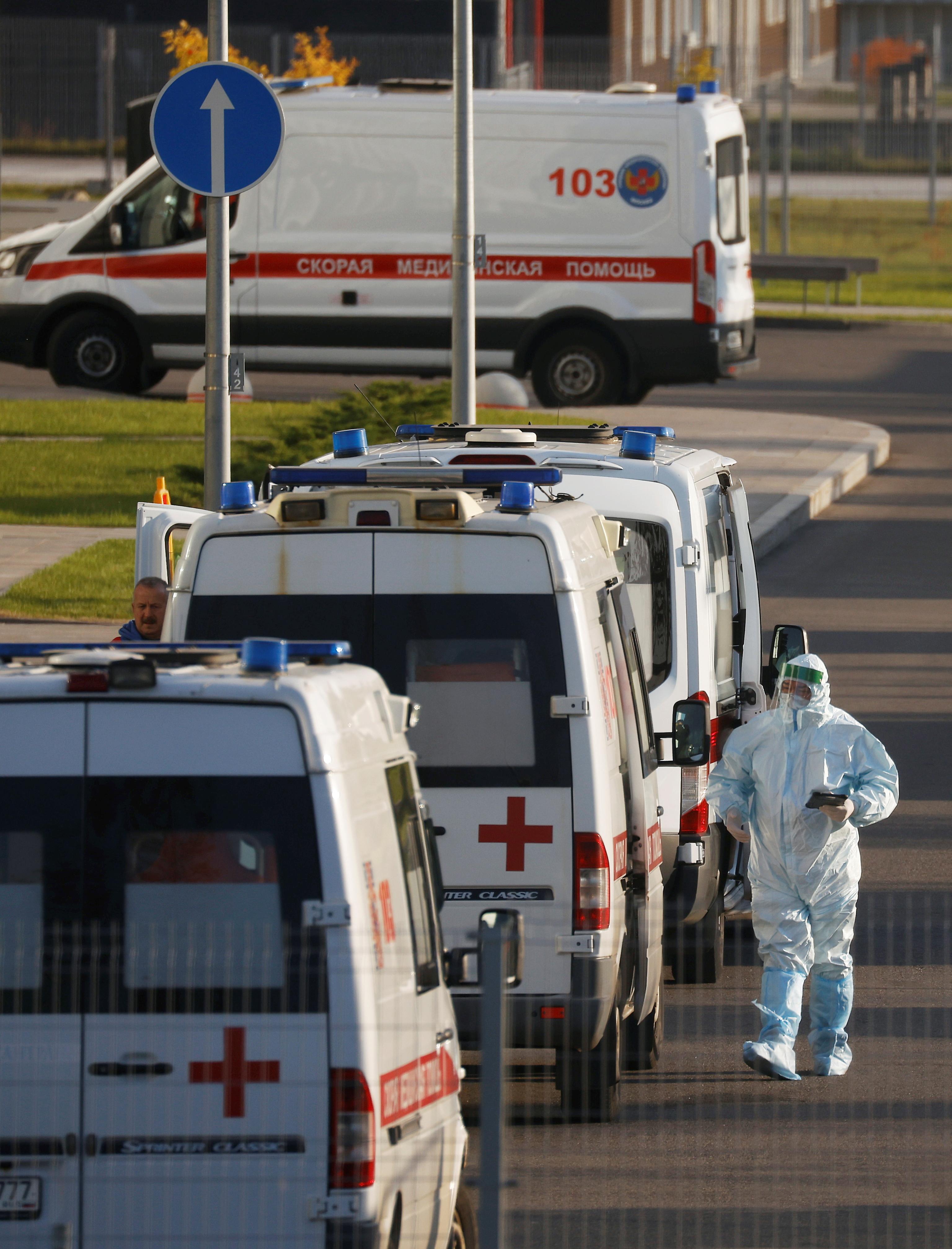 Un médico especialista pasa por ambulancias con gente infectada de Covid-19.