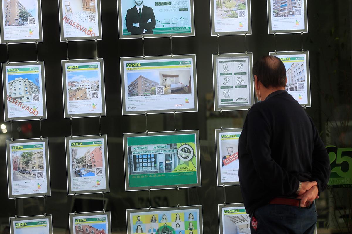Un ciudadano mira pisos en oferta en el escaparate de una agencia inmobiliaria.