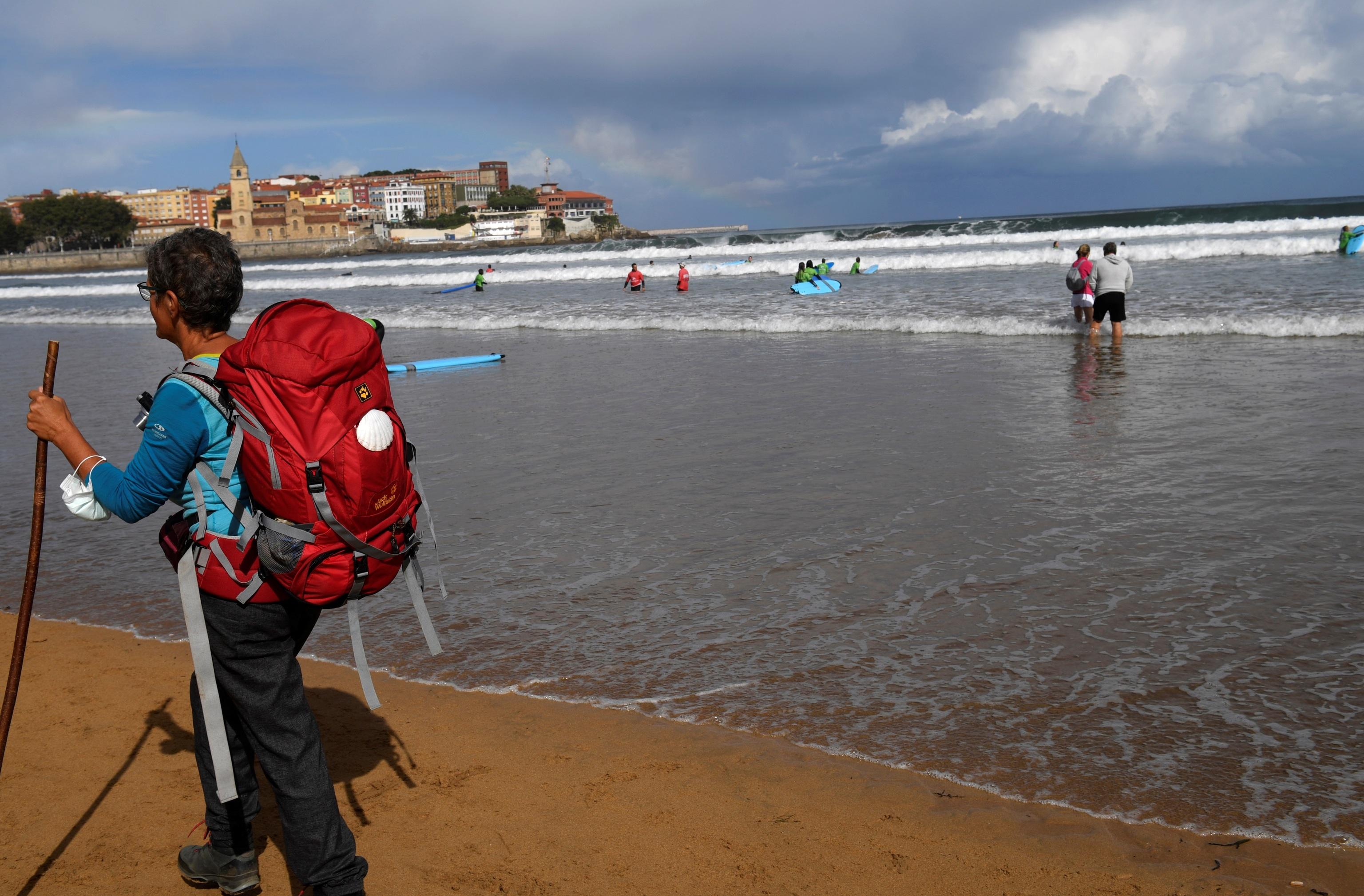 Una mujer pasea por la playa de San Lorenzo de Gijón.