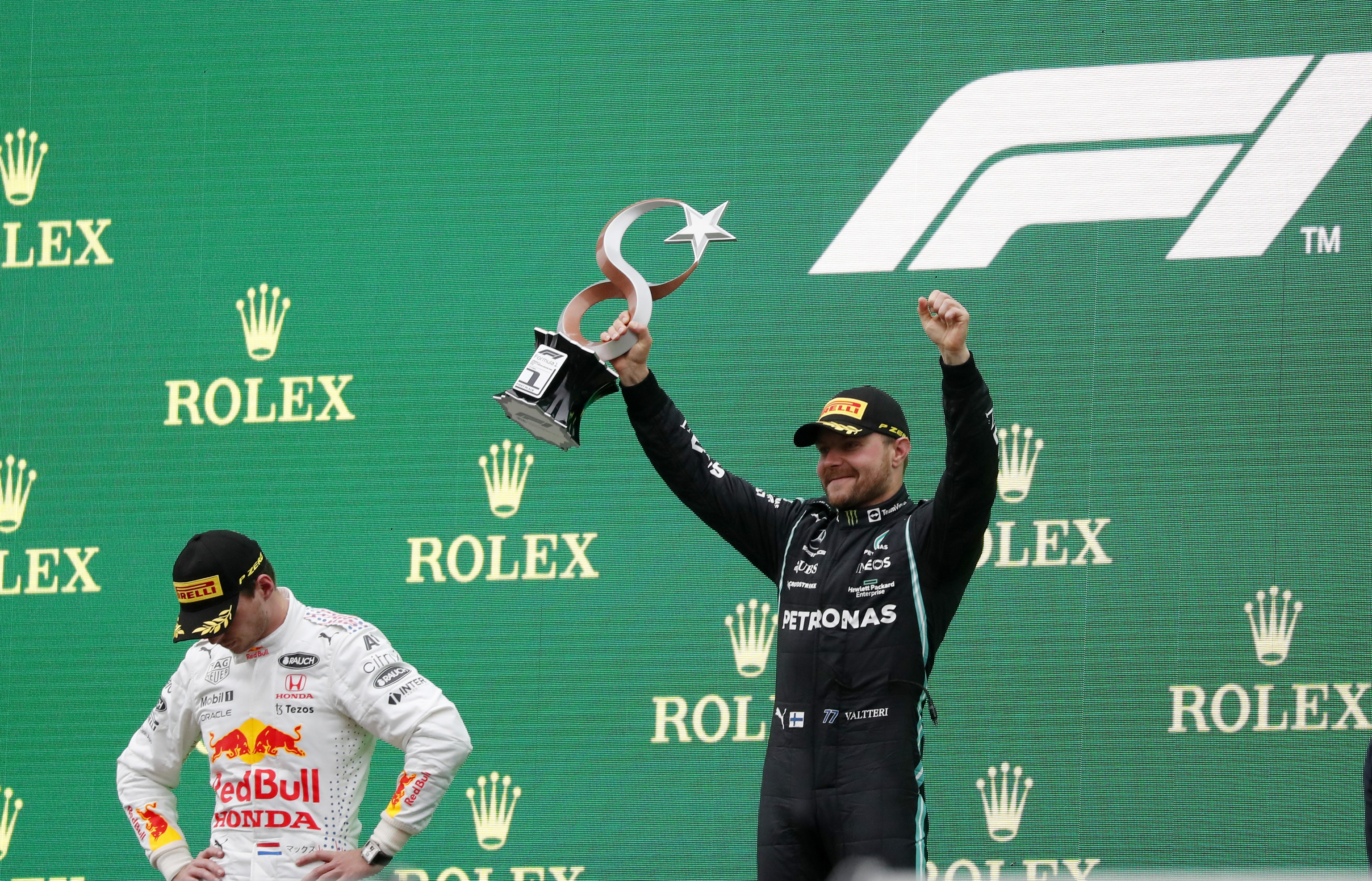 Bottas, en el podio, junto a un cabizbajo Verstappen.