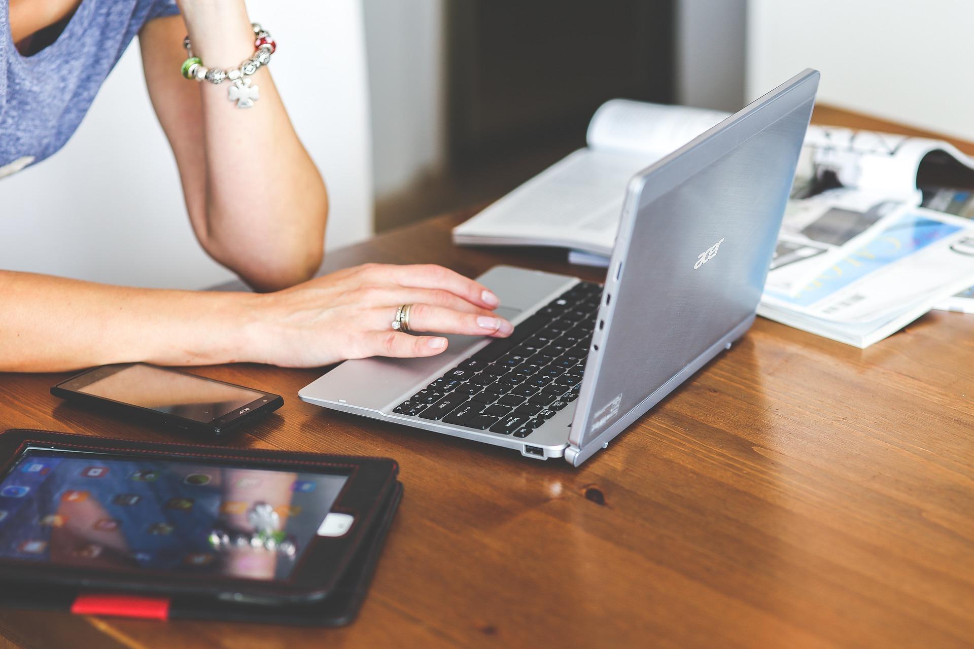 Una mujer se encuentra utilizando el ordenar portátil junto a un teléfono móvil y una tablet.