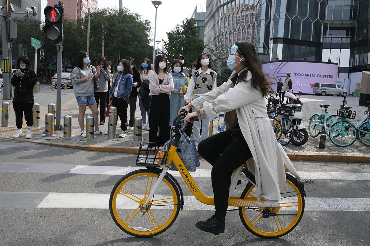 Una mujer en bici con dos mascarillas en Pekín.